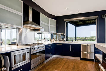 Picture of a blue appliance and counter top kitchen. looks very modern.
